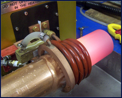 Photo shows copper tube annealing at the end of the heating stroke. Quench ring's water spray is activated to prevent heat zone from moving beyond the required area.
